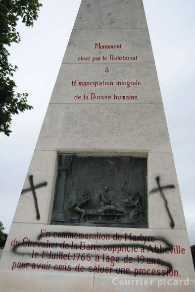 [A photo showing the vandalism of the Chevalier de la Barre obelisk in Abbeville. The inscription is crossed out, and crosses are painted onto the obelisk.]