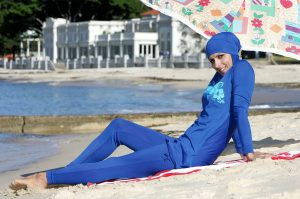 [A photo of a model posing sitting on the beach in a blue burqini.]
