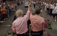 """[A screen capture from the Jim Egan """"Heritage Minute"""", showing footage from the 1995 Toronto Pride Parade, with a shot of Jim Egan and John Nesbit from behind, riding high in a convertible in the parade with cheering crowds on either side. Egan and Nesbits arms are raised, and they are holding hands.]"""